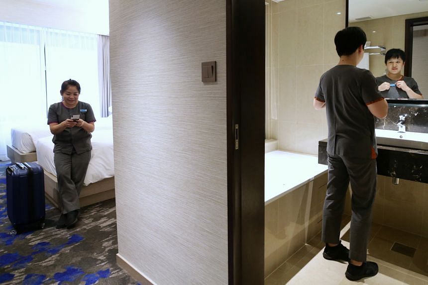 Housekeeping attendants Wen Shu Jun (left), 52, and Rita Hou Qixin, 29, in a hotel room last week in Royal Plaza on Scotts, which opened up its rooms for staff who were sharing rented apartments with other foreign workers placed on leave of absence.