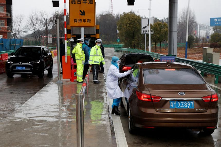 A medical worker checks a driver's temperature at a checkpoint in Susong, China, on Feb 6, 2020.