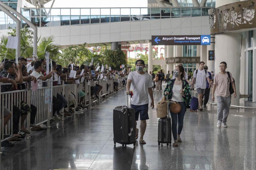 Passengers wear face masks at Ngurah Rai International Airport in Bali on Feb 9, 2020.