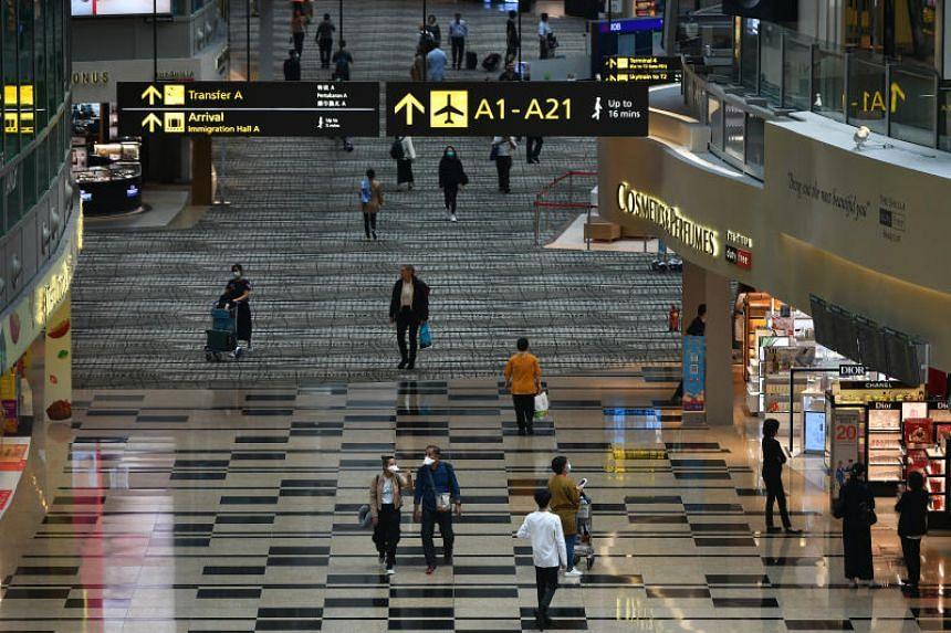 Passengers wearing face masks walk inside the transit area of Changi Airport Terminal 3 on Feb 12, 2020.