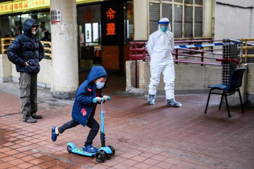 A child riding his scooter past Hong Mei House at Cheung Hong Estate in Hong Kong on Feb 11, 2020. Dozens of residents were evacuated from their apartment building after two people living 10 floors apart were found to be infected with the coronavirus