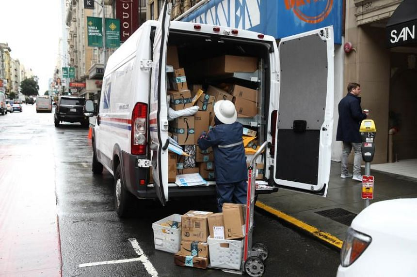 A US Postal Service worker unpacks packages from a truck in San Francisco on Dec 2, 2019.