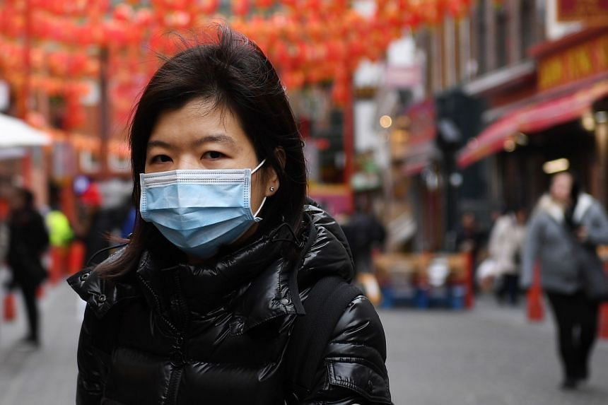 A woman wears a face mask in Chinatown in London, Feb 4, 2020.