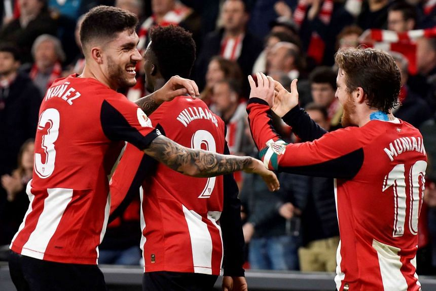 Athletic's winger Iker Muniain (R) celebrates with his teammates after scoring.