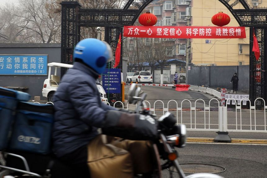 """A food delivery man rides his motorcycle past a banner reading """"Unite as one, firm confidence, scientific prevention and control, and defeat the epidemic"""" in Beijing, China."""