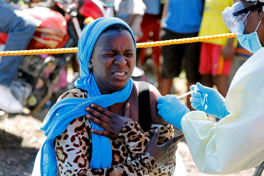 In an August 2019 photo,  a  young woman reacts as a health worker injects her with the Ebola vaccine.