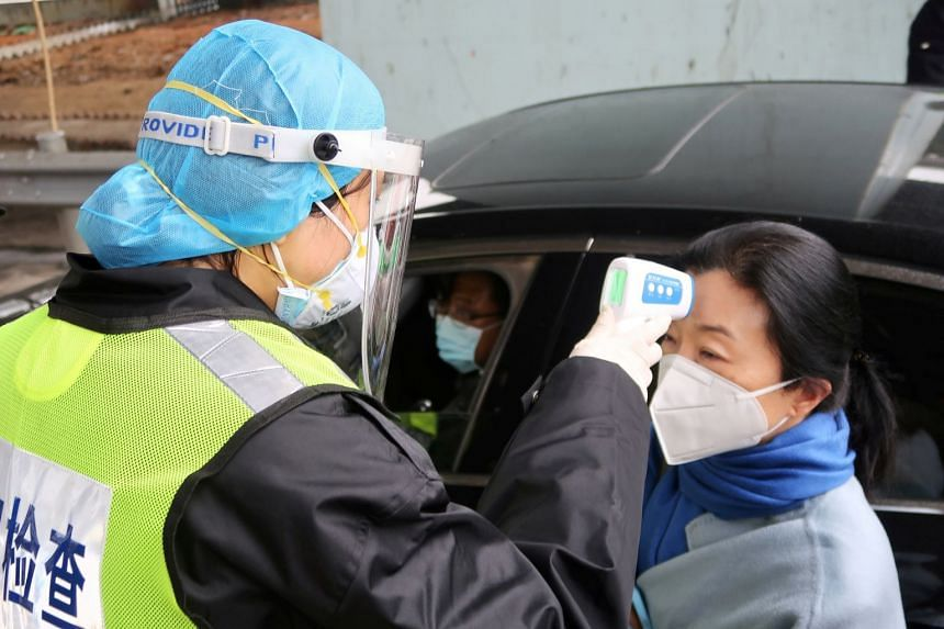 A security officer in a protective mask checks the temperature of a passenger at an expressway toll station in Xianning, Hubei province.