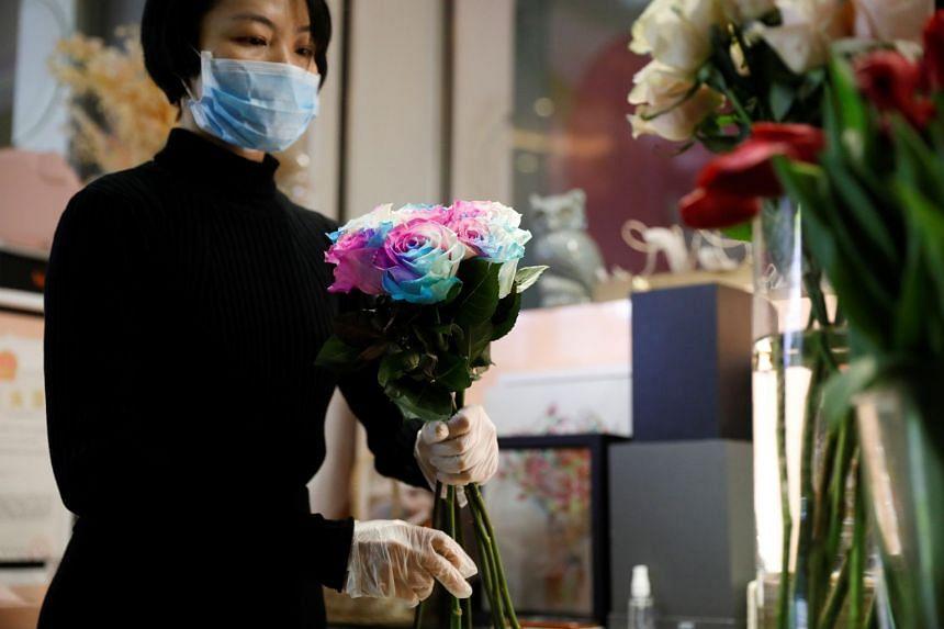 Florist Cai Xiaoman, wearing a protective face mask and gloves, assembles a bouquet.