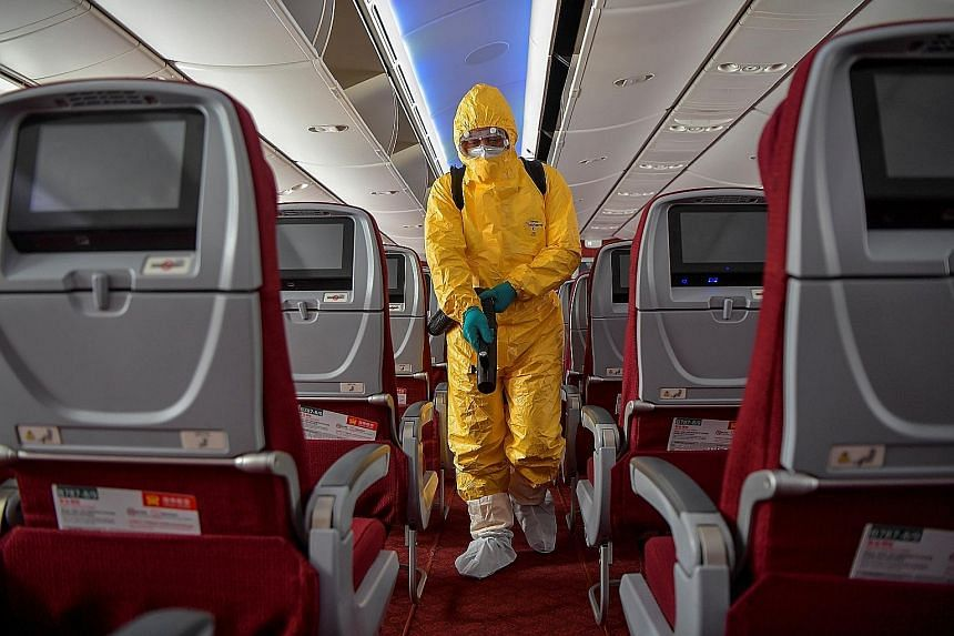 A man in a protective suit disinfecting the cabin of a Hainan Airlines flight at the Haikou Meilan International Airport in China's Hainan province last Friday. PHOTO: REUTERS