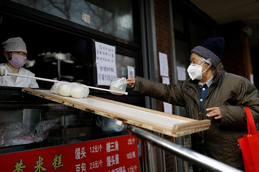 A customer placing money into a container on a stick held out by an employee at a restaurant in Beijing yesterday, while food is passed to customers along a makeshift ramp, in a bid to minimise contact as China deals with the coronavirus outbreak. A