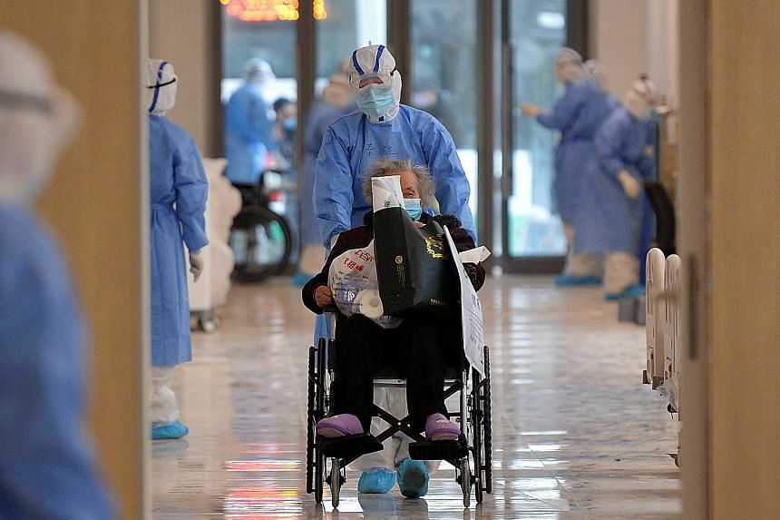 A medical worker with a coronavirus patient in a Wuhan hospital on Monday. The city faced a daily shortage of 41,000 protective suits last week.