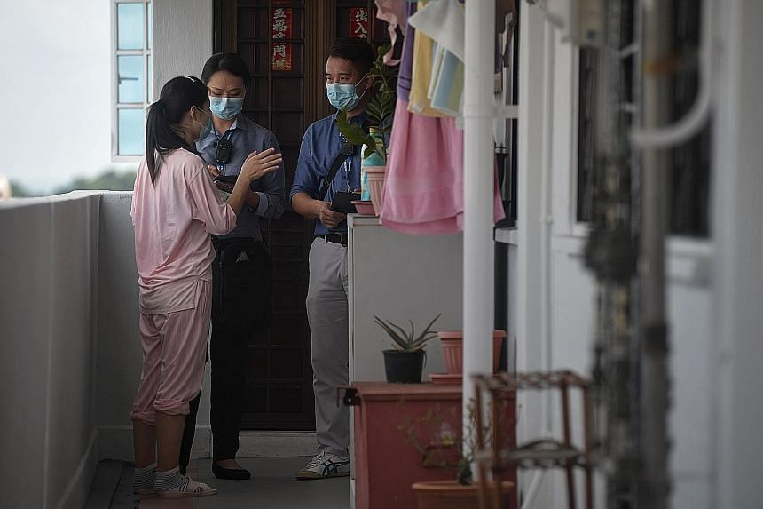 Mr Keith Aw, 41, and Ms Ong Peishi, 36, from the Ministry of Manpower's (MOM) foreign manpower management division, checking on a work pass holder who is nearing the end of her mandatory leave of absence (LOA) at her Bedok flat yesterday. People on t
