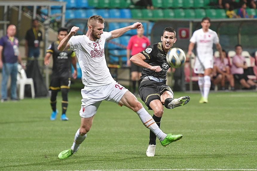 Tampines Rover striker Boris Kopitovic (right) squaring off against PSM Makassar midfielder Serif Hasic during their AFC Cup Group H match at the Jalan Besar Stadium last night. Goals by Jordan Webb (24th minute) and Kopitovic (64th) gave the dominan
