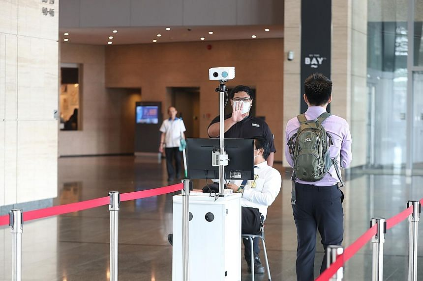 A thermal scanner at the entrance of Marina Bay Financial Centre Tower 3. The 300 employees working on the 43rd floor, the same floor as a man confirmed to be infected with the virus, left by 12pm yesterday. ST PHOTO: TIMOTHY DAVID