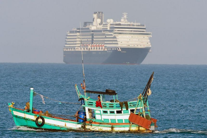 The Westerdam cruise ship (top) is seen past a fishing vessel as it approaches port in Sihanoukville on Cambodia's southern coast, on Feb 13, 2020.