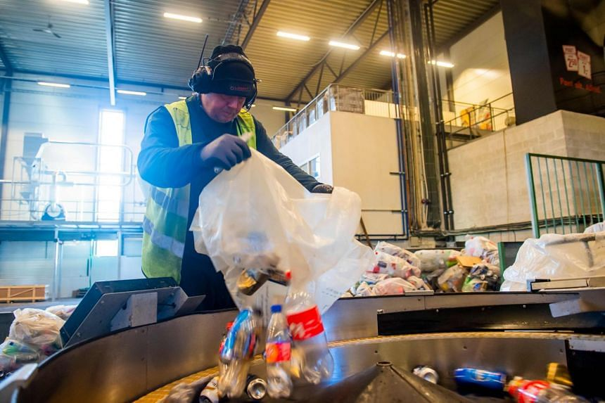 A worker pours plastic bottles and aluminium cans into a machine at a recycling plant, in Fetsund, Norway, on Jan 21, 2020.