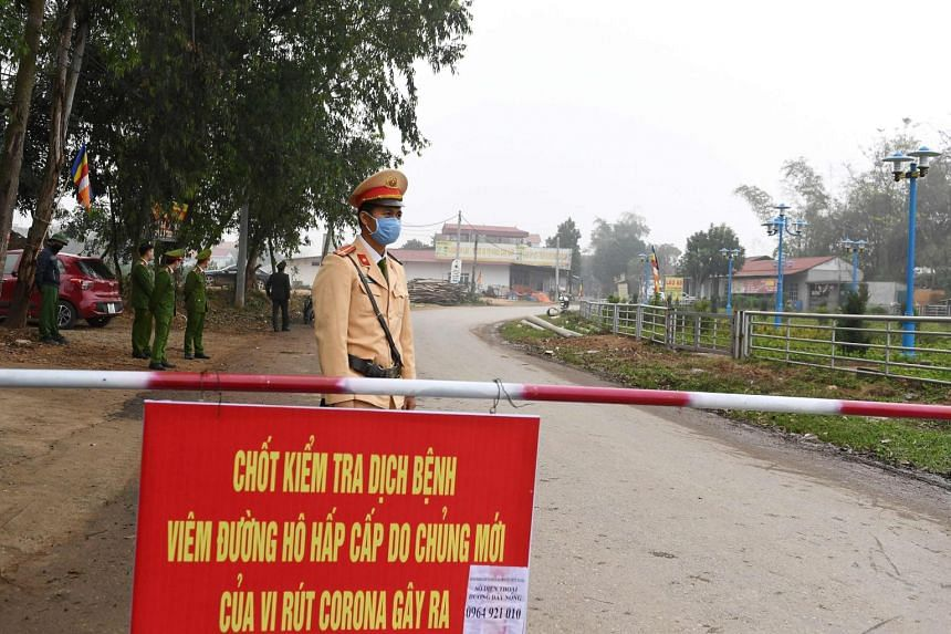 A police official wearing a protective face mask amid concerns of the coronavirus outbreak stands guard at a checkpoint in Son Loi commune in Vinh Phuc province, Vietnam, on Feb 13, 2020.