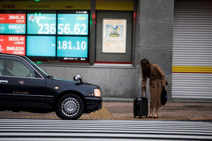 A woman hails a taxi in Tokyo on Dec 30, 2019. A male Japanese taxi driver in Tokyo has tested positive for the coronavirus.
