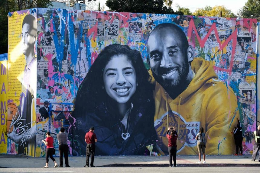 People take pictures of a mural of late NBA legend Kobe Bryant and his daughter Gianna in Los Angeles.