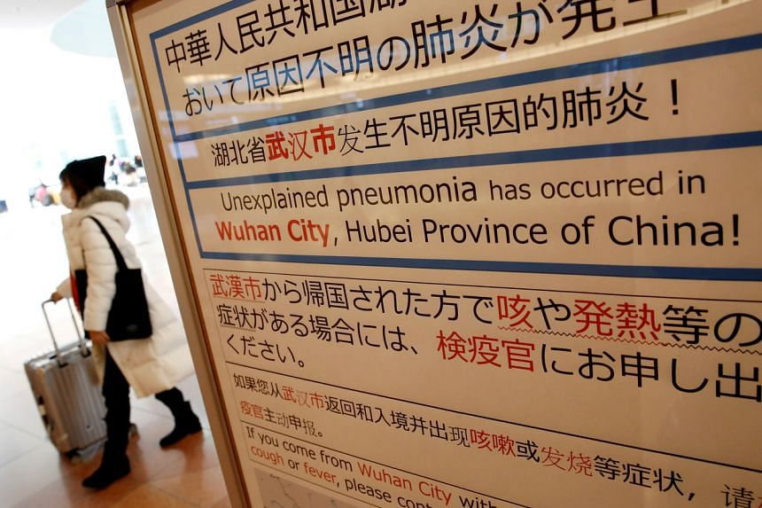 A notice about the outbreak of the coronavirus at an arrival hall of Haneda airport in Tokyo. A woman in her 80s has become the first person with the coronavirus to die in Japan.