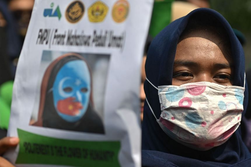 An Indonesian protester displays a poster during a rally to show support for the Uighur minority in China, outside the Chinese embassy in Jakarta on Dec 20, 2019.