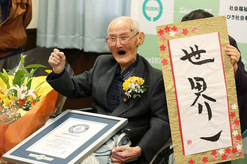 """Chitetsu Watanabe poses next to calligraphy reading in Japanese """"World Number One""""."""