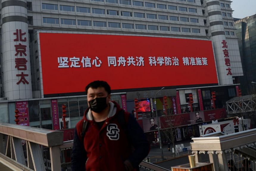 """A man wearing a face mask stands near a giant screen showing a slogan that reads """"Strengthen confidence, work together, prevent and cure with science, implement measures with precision"""" in Beijing on Feb 11, 2020."""