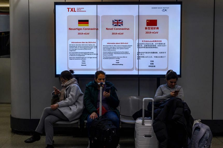 In a photo from Jan 28, 2020, passengers sit in front of an electronic billboard displaying information on the coronavirus at Berlin's Tegel airport.
