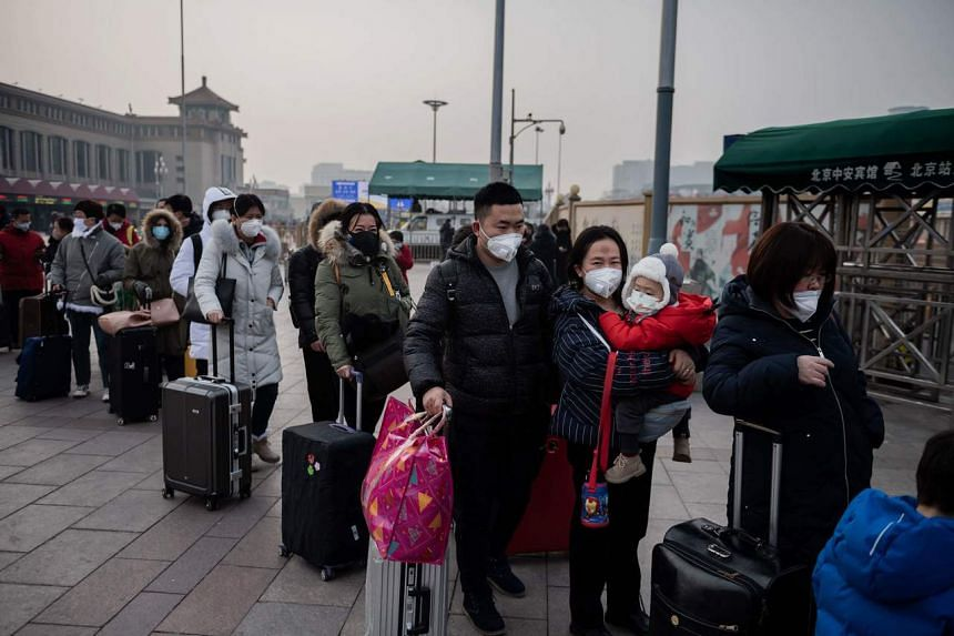 In this photo taken on Jan 27, 2020, people wearing protective masks queue to take a taxi at the Beijing railway station.