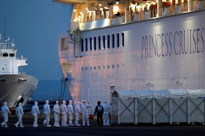Officers in protective gear enter the cruise ship Diamond Princess at Daikoku Pier Cruise Terminal in Yokohama, south of Tokyo, on Feb 7, 2020.