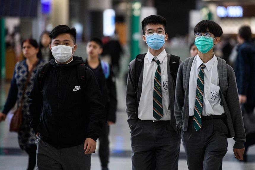 Students wear face masks in the arrival hall at Hong Kong's international airport on Jan 22, 2020.