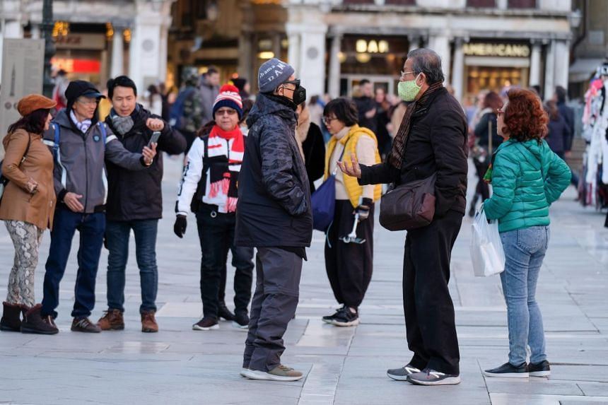 Tourists wear protective masks in St. Mark's Square in Venice, Italy, on Feb 6, 2020.