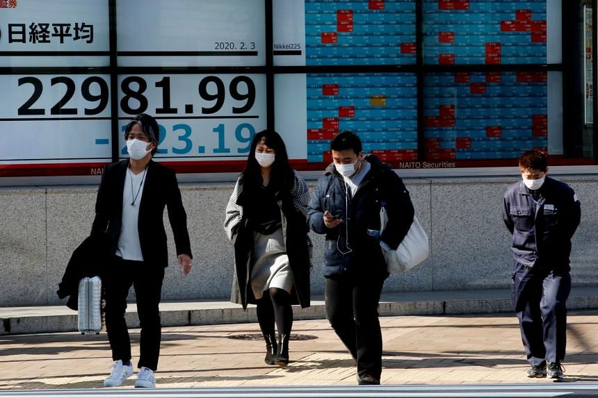 People wearing surgical masks walk past a screen showing the Nikkei index outside a brokerage in Tokyo, Japan, on Feb 3, 2020.