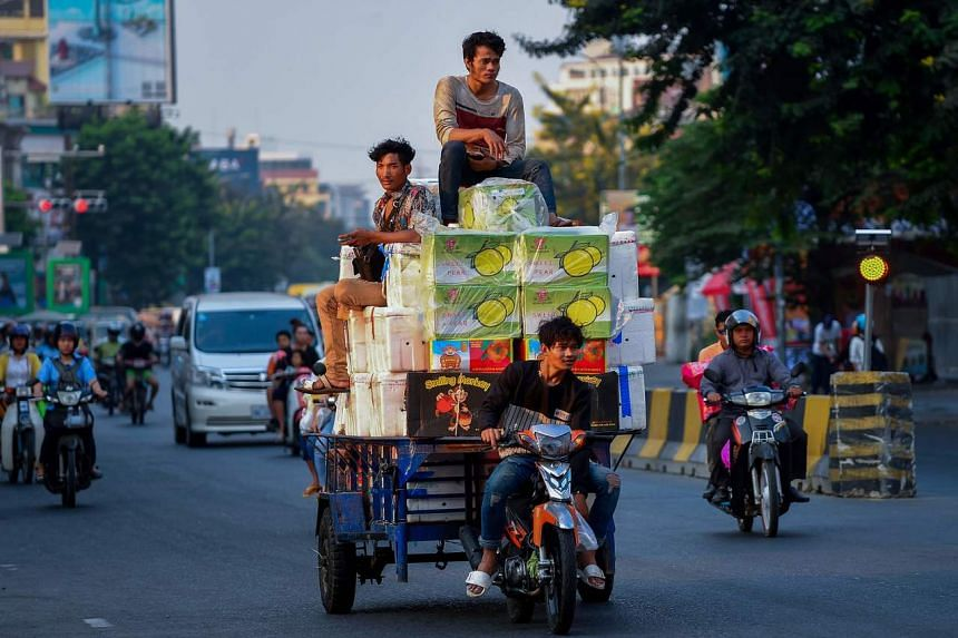 Men transporting boxes of goods on motorcycle cart along a street in Phnom Penh, on Jan 22, 2020.