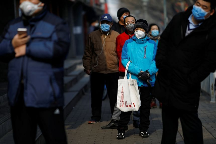 Customers wearing face masks queue for food outside a store in Beijing on Feb 12, 2020.