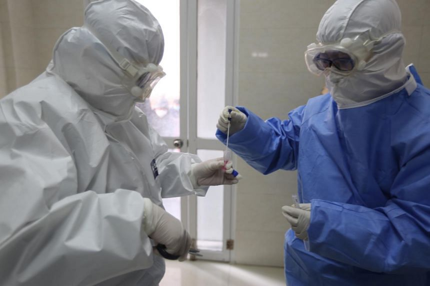 A doctor puts a swab taken from a woman into a tube for coronavirus testing in a fever clinic in Yinan county, in east China's Shandong province, on Feb 12, 2020.