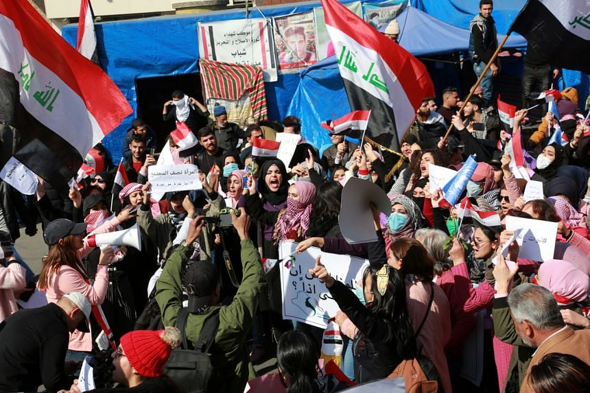 Iraqi women carry Iraqi national flags and chant slogans during a protest at the Al-Tahrir square in central Baghdad, Iraq, on Feb 13, 2020.