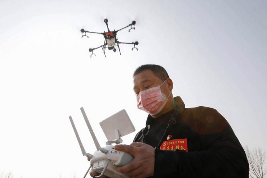 A man using a drone to spray disinfectant  on Jan 31, 2020, in a village in Pingdingshan, in China's central Henan province.