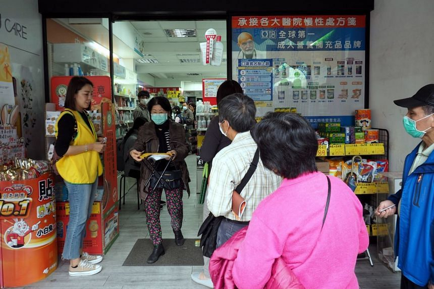 People queue up to buy face masks at a pharmacy in Taipei, Taiwan.