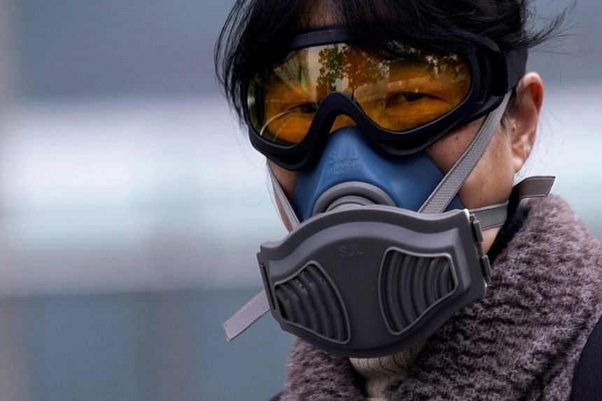 A woman wearing a mask is seen at a subway station in Shanghai, China.