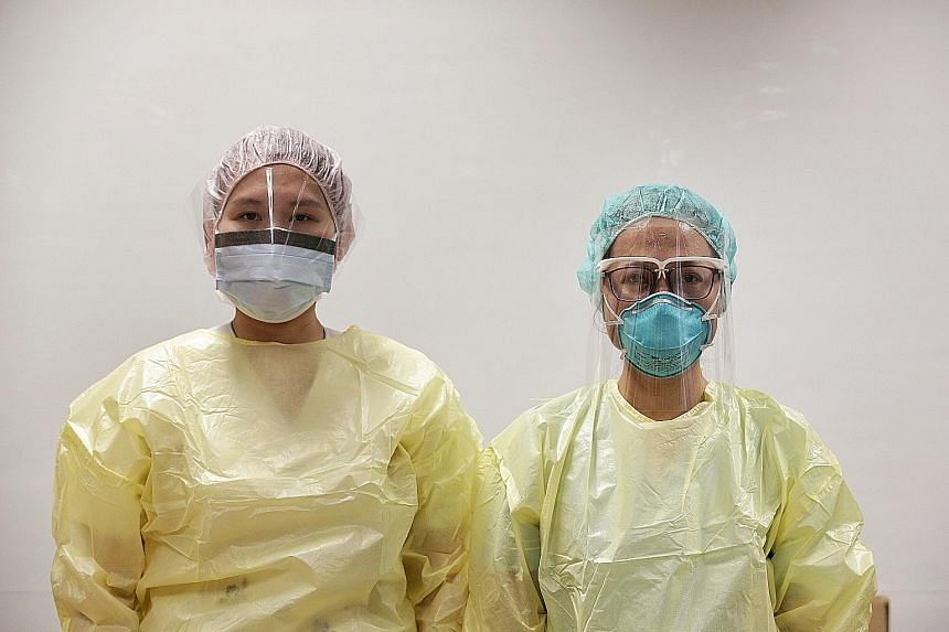 A nurse (right) donning the new face shield prototype which comes with a frame that leverages 3D-printing technology, while another wears the face visor that healthcare staff can currently opt for in lieu of wearing protective goggles. ST PHOTO: KEVI