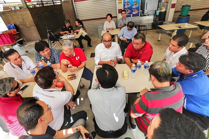 Senior Minister of State for Transport Janil Puthucheary (centre), with Mr Ang Hin Kee (third from left), adviser to the National Taxi Association and National Private Hire Vehicles Association, speaking to drivers yesterday about the relief package,