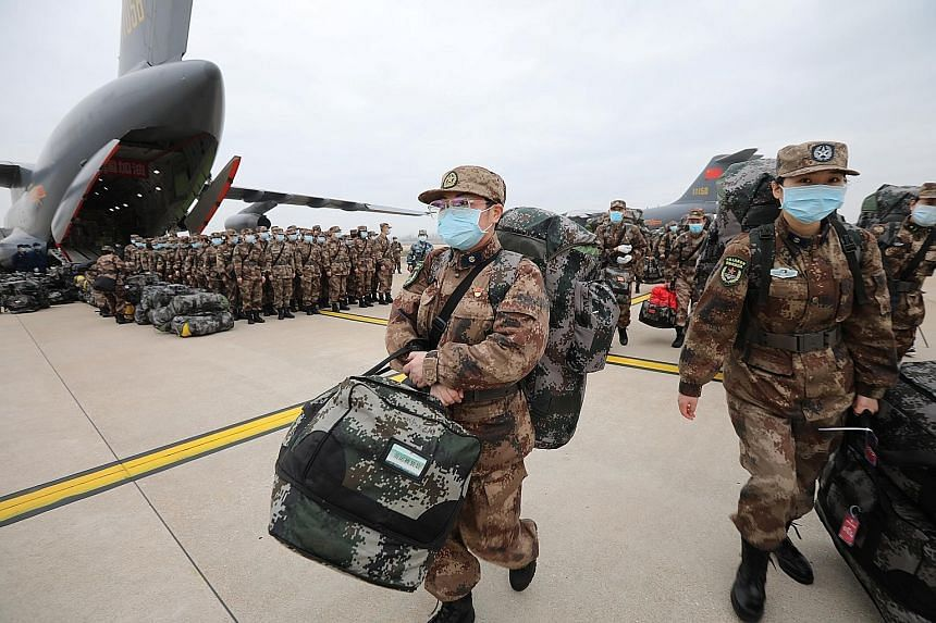 Personnel with medical supplies disembarking from Chinese People's Liberation Army Air Force planes at the Wuhan Tianhe International Airport in Hubei province yesterday.