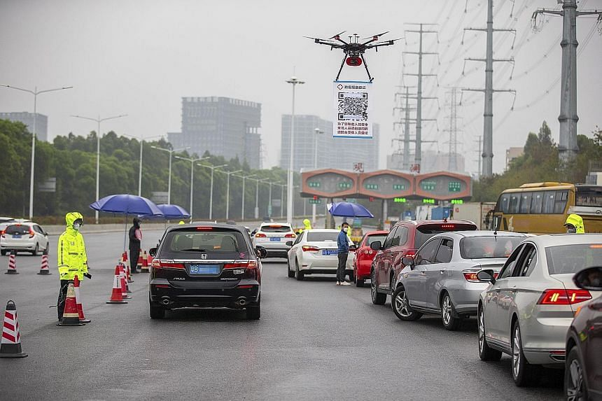 A drone with a QR code poster broadcasting audio messages asking motorists to scan the code and register their details online, to minimise contact with personnel and speed up inspection, in Shenzhen, in southern Guangdong province, on Tuesday.