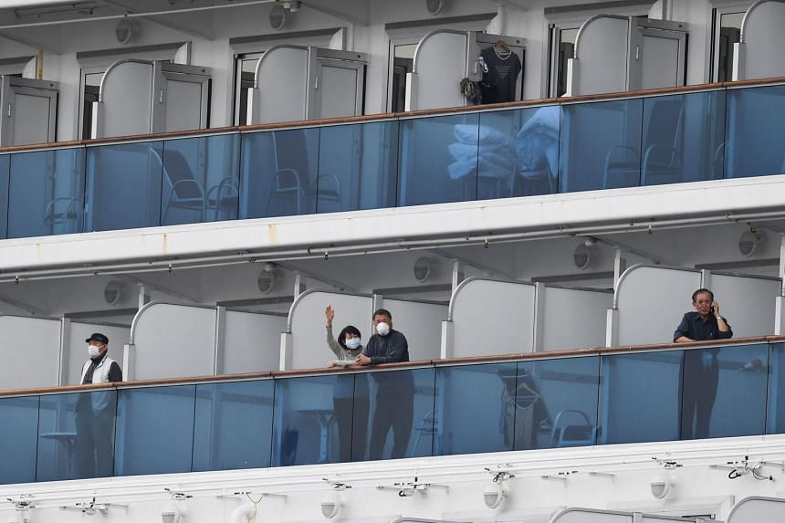 Passengers look out from their balconies on the Diamond Princess cruise ship at the Daikoku Pier Cruise Terminal in Yokohama, on Feb 14, 2020.