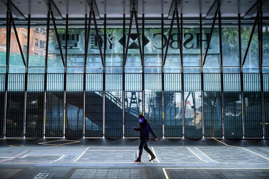 A man wearing a face mask walks within the shuttered local HSBC headquarters building in Hong Kong, on Jan 31, 2020.