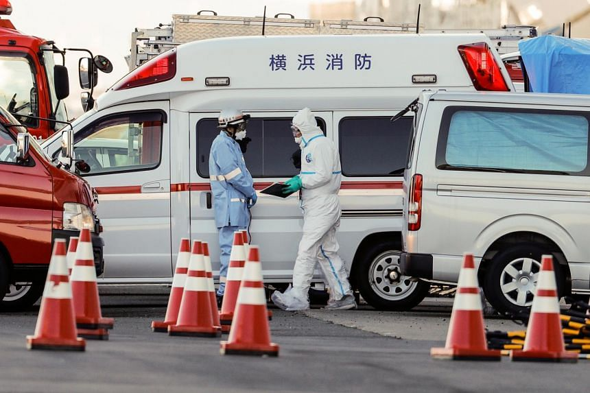 Officials in protective gear preparing to transfer passengers from the cruise ship Diamond Princess to a hospital, in Yokohama, on Feb 6, 2020.