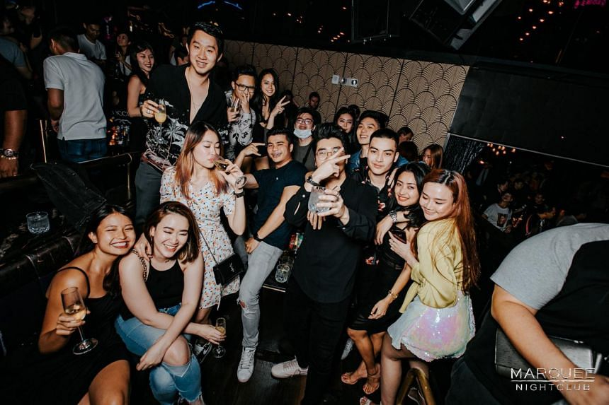 A partygoer wearing a mask (centre) as DJ Illenium spins at Marquee Singapore, on Feb 8, 2020.
