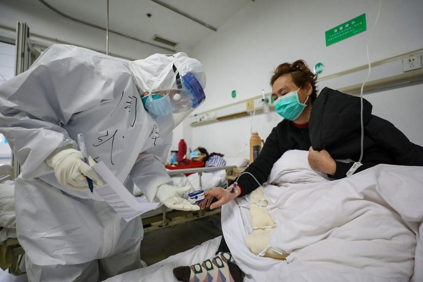 A doctor checking the oxygen saturation of a patient at Jinyintan Hospital, in Wuhan, Hubei province, China, on Feb 13, 2020.