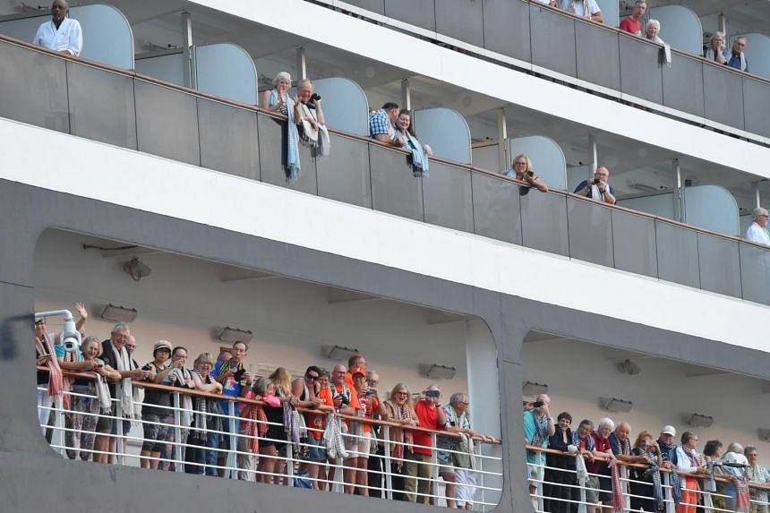Passengers on board the Westerdam cruise ship look on in Sihanoukville, on Feb 14, 2020.